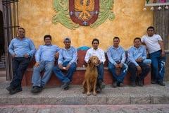 Grupo de homens de assento que levantam com um cão Imagem de Stock