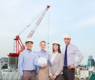Grupo de homens de negócios de sorriso nos capacetes brancos Imagens de Stock Royalty Free