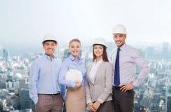 Grupo de homens de negócios de sorriso nos capacetes brancos Foto de Stock Royalty Free