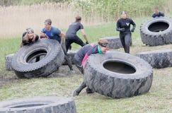 Grupo de homens e de mulher que esforçam-se para derrubar um grande pneu do trator Foto de Stock Royalty Free