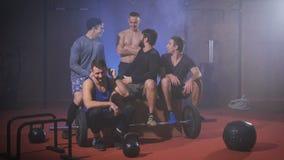 Grupo de homens fortes no gym que tem a arma após o treinamento do crossfit filme