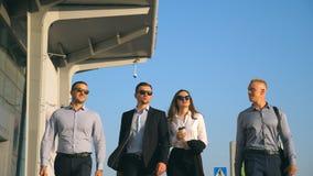 Grupo de homens de negócios felizes novos que andam na rua da cidade ao terminal de aeroporto Colegas que estão em sua maneira ao vídeos de arquivo