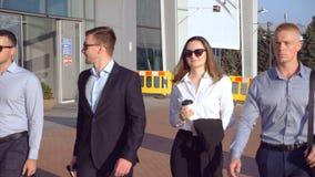 Grupo de homens de negócios novos que andam ao aeroporto no dia ensolarado Colegas que estão em sua maneira à viagem de negócios  vídeos de arquivo