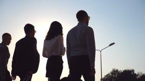 Grupo de homens de negócios novos que andam na rua da cidade no tempo do por do sol Colegas que estão em sua maneira de dirigir a video estoque