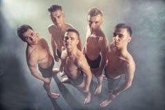 Grupo de homens novos dos dançarinos que levantam-se e que olham na câmera no estúdio no fundo fumarento preto Fotos de Stock