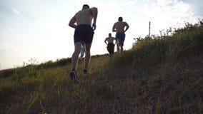 Grupo de homens novos que correm acima o monte verde sobre o céu azul com o alargamento do sol no fundo Os atletas masculinos est video estoque