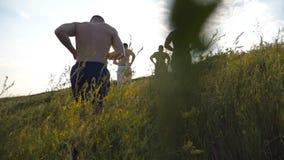 Grupo de homens novos que correm acima o monte verde sobre o céu azul com o alargamento do sol no fundo Os atletas masculinos est filme