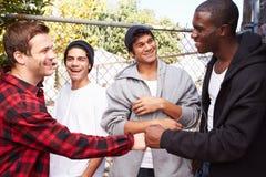 Grupo de homens novos que cumprimentam um outro em S urbano foto de stock