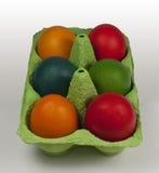 Grupo de huevos de Pascua coloreados en el portador del huevo Fotos de archivo libres de regalías