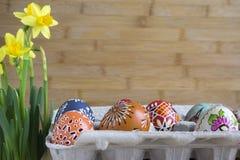 Grupo de huevos de Pascua con las diversas pinturas cerosas, los pequeños agujeros y las imágenes en el cartón de huevos de papel imagenes de archivo
