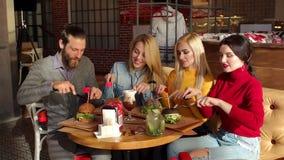 Grupo de inconformistas que comen las hamburguesas hermosas del pan negro con el cuchillo y la bifurcación almacen de metraje de vídeo