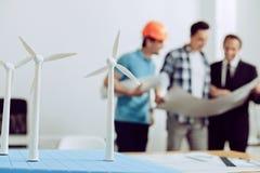 Grupo de ingenieros expertos que trabajan en los generadores del molino de viento fotografía de archivo