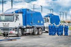 Grupo de internos en el entrenamiento de campo del cable metálico de Schlumberger al lado de dos camiones del cable metálico Imagenes de archivo