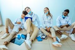 Grupo de internos médicos esgotados que sentam-se no assoalho no hospital fotografia de stock