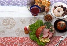 Grupo de jantar tradicional de easter com carne cortada com limão e ervas, pão, ovos coloridos feitos a mão, chocolates, passas,  Imagem de Stock