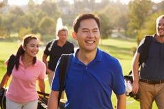 Grupo de jogadores de golfe que andam ao longo dos sacos de golfe levando do fairway Fotos de Stock Royalty Free