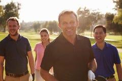 Grupo de jogadores de golfe que andam ao longo dos sacos de golfe levando do fairway fotografia de stock