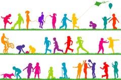 Grupo de jogo colorido das silhuetas das crianças exterior Foto de Stock