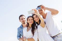 Grupo de jovens alegres e bonitos que tomam fotos do th Imagem de Stock