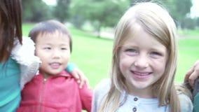 Grupo de jovens crianças de sorriso novas que olham na câmera