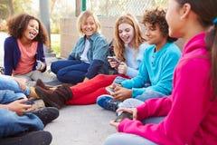 Grupo de jovens crianças que penduram para fora no campo de jogos Foto de Stock