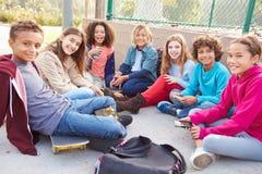 Grupo de jovens crianças que penduram para fora no campo de jogos Imagens de Stock