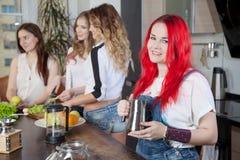 Grupo de jovens mulheres em uma preparação da sala da cozinha Fotos de Stock Royalty Free