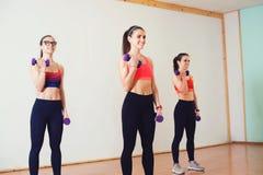 Grupo de jovens mulheres no sportswear com pesos que exercitam no gym imagens de stock