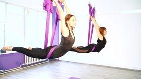 Grupo de jovens mulheres que fazem a ioga do ar com uma rede no estúdio filme