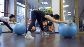 Grupo de jovens mulheres que fazem o exercício aeróbio com um fitball azul filme