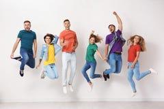 Grupo de jovens nas calças de brim e em t-shirt coloridos fotografia de stock royalty free