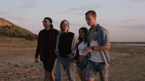 Grupo de jovens que andam pela estrada arenosa perto do mar ou do lago Sorriso, comunicando-se Pares novos Vestir ocasional video estoque