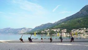 Grupo de jovens que estão em asanas da ioga na praia vazia do mar na manhã filme