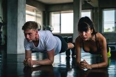 Grupo de jovens que fazem exerc?cios no gym foto de stock
