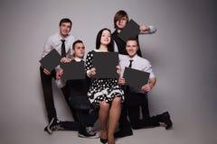 Grupo de jovens que guardam folhas de papel Imagens de Stock Royalty Free