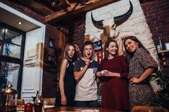 Grupo de jovens que levantam na posição da câmera, sorrindo, riso, fazendo as caras ao ter o divertimento no restaurante na moda foto de stock royalty free