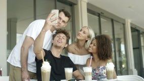 Grupo de jovens que sentam-se em um restaurante e em uma tomada selfies filme