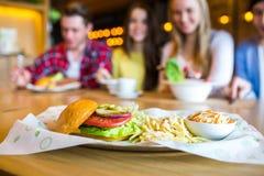 Grupo de jovens que têm o divertimento no café, foco na refeição Imagens de Stock Royalty Free