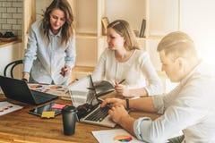 Grupo de jovens que trabalham junto O homem está usando o portátil, meninas que olham na tela do portátil, discutindo o plano de  imagem de stock
