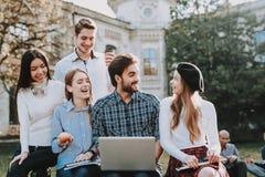 Grupo de jovens sente-se pátio universidade imagens de stock royalty free