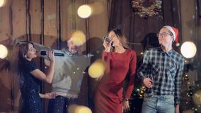 Grupo de Joyfull de amigos que bailan que canta celebrando la Navidad partido del Año Nuevo almacen de video