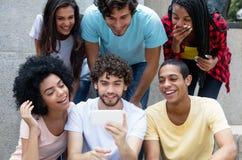 Grupo de juego joven internacional de los adultos con el teléfono foto de archivo libre de regalías