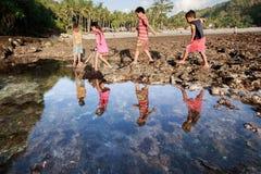 Grupo de juego de niños pobre de la pobreza en la playa foto de archivo