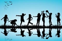 Grupo de jugar de las siluetas de los niños al aire libre Fotografía de archivo libre de regalías