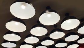 Grupo de lámparas iluminadas metal negro moderno que cuelgan en el techo Fotografía de archivo libre de regalías