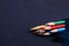 Grupo de lápis coloridos envolvidos em uma fita azul no fundo preto De volta à escola Copie o espaço Imagem de Stock Royalty Free