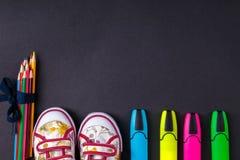 Grupo de lápis coloridos envolvidos em uma fita azul perto das sapatilhas e do marcador no fundo de madeira preto De volta à esco Fotos de Stock Royalty Free