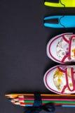 Grupo de lápis coloridos envolvidos em uma fita azul perto das sapatilhas e do marcador no fundo de madeira preto De volta à esco Imagens de Stock