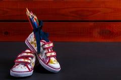 Grupo de lápis coloridos envolvidos em uma fita azul perto das sapatilhas no fundo de madeira preto De volta à escola Copie o esp Imagem de Stock Royalty Free