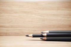 Grupo de lápiz agudo del color negro en el fondo de madera uno de hacia fuera Foto de archivo